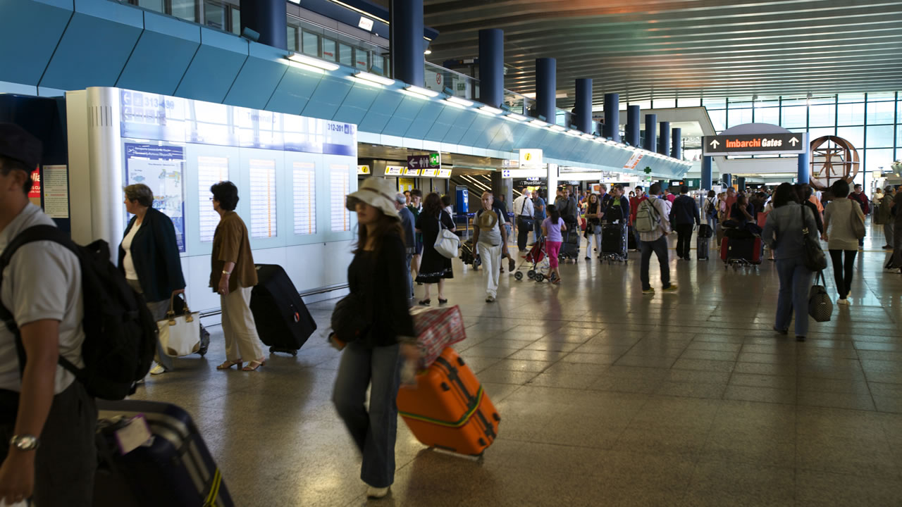 Passengers departing from Rome-Fiumicino airport, inside the Terminal 3 of air terminal.