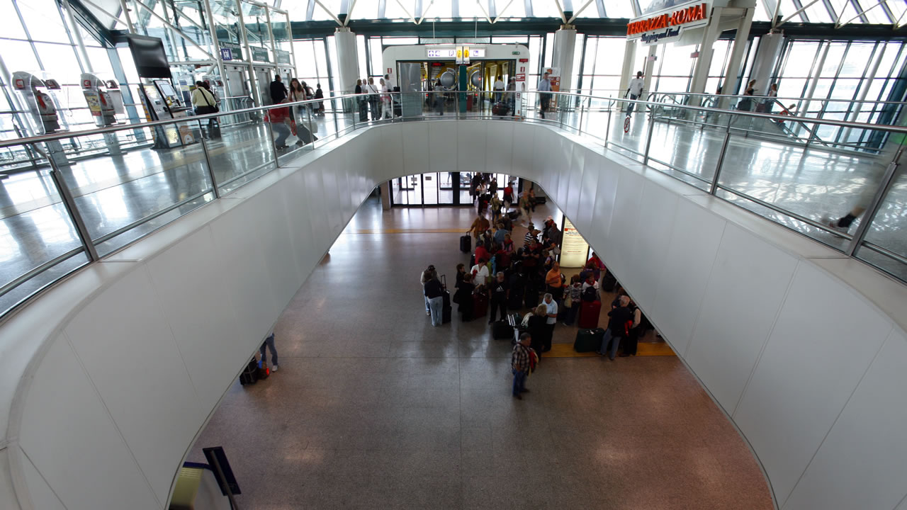 Detail shot of the Terrazza Rome at Terminal 3 of Leonardo da Vinci airport, overlooking the lower level with passengers waiting at the meeting place for groups.