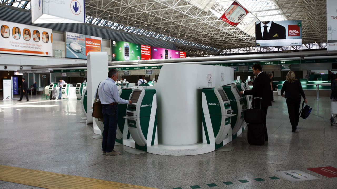 Interior of Terminal 1 at Rome-Fiumicino airport, with passengers at Alitalia desks of fast check-in.